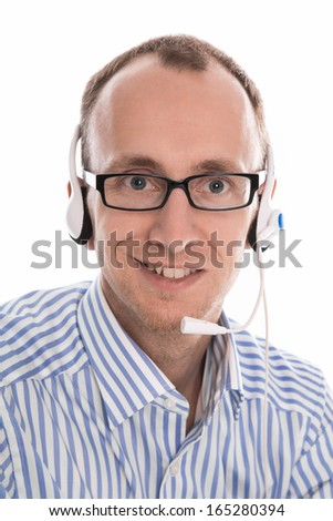 Helpful man with headset smiling at camera working in a call-center. - stock photo