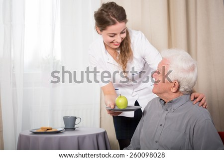 Helpful nurse and smiling pensioner at home - stock photo