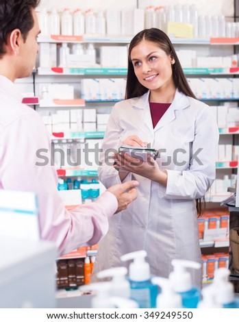 Helpful pharmacist serving and consulting man at the pharmacy  - stock photo