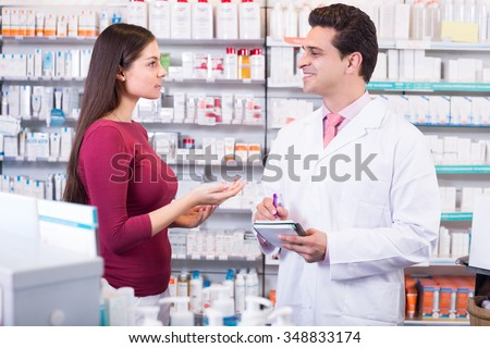 Helpful pharmacist serving young female in pharmacy and smiling - stock photo