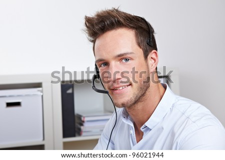 Helpful phone support agent with headset in callcenter office - stock photo