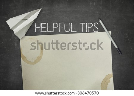 Helpful tips concept on black blackboard with empty paper sheet and coffee cup - stock photo