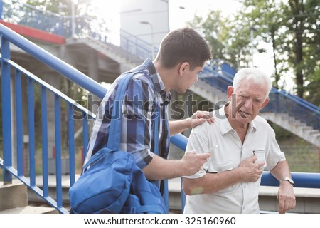 Helpful young man talking with male retiree - stock photo