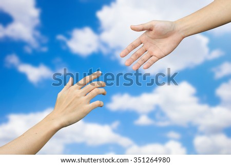helping/assistance hand and on blurred blue sky and clouds backgrounds.helping hand concept:hospitality of human's life conceptual.adore liberality of humanity conception.love ,hopeful and care. - stock photo