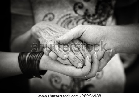 Helping elderly people concept - young hands supporting old hand - stock photo