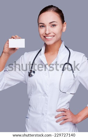 Helping every person who calls me. Confident female doctor in white uniform holding business card and looking at camera and smiling while standing against grey background