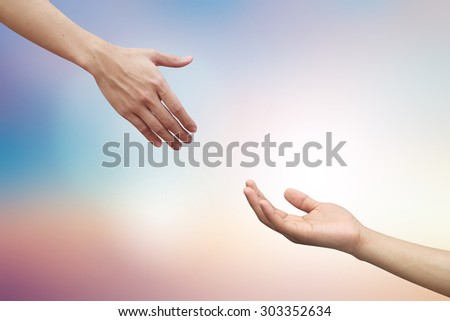 helping hand and hands praying on blurred beautiful twilight sky backgrounds. helping hand concept.hand of god giving the power to human's hand. - stock photo