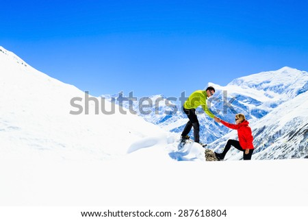 Helping hand couple, hiking help each other. Man and woman climbing or hiking with motivation and inspiration, beautiful inspirational landscape. Extreme sports and fitness, wilderness in Nepal. - stock photo