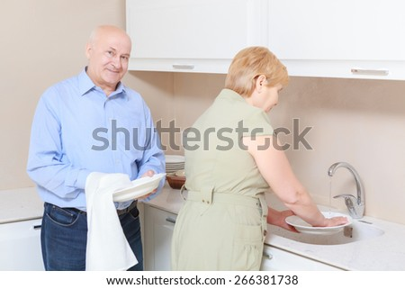 Helping hand. Happy senior couple washing dishes at home in the kitchen - stock photo