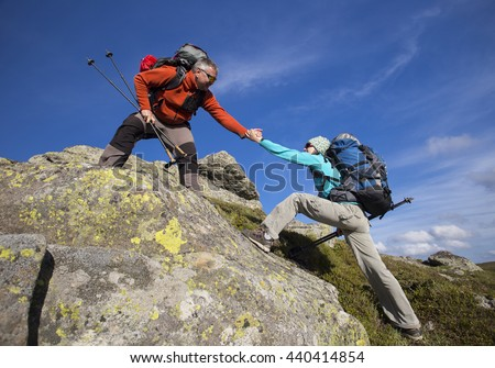 Helping hand - hiker woman getting help on hike smiling happy overcoming obstacle. - stock photo
