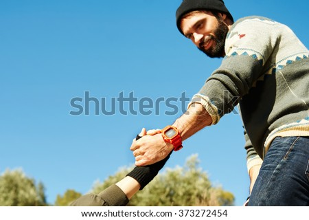 Helping hand hiking girl get help from a smiling man focus at hands on hike happy overcoming obstacle. Active lifestyle hiker couple traveling. Focus on hands - stock photo