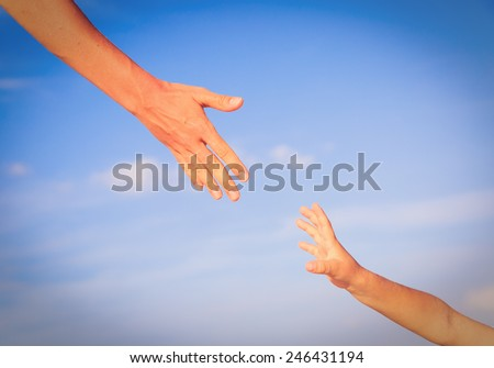 helping hand of mother and child on sky, care and protection - stock photo