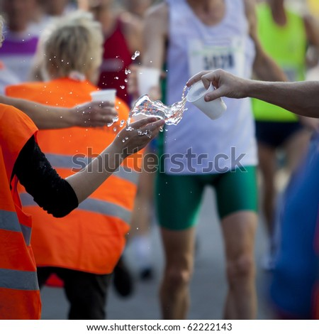 Helping hand providing water for refreshment during marathon race