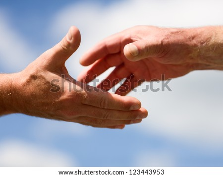 Helping hand. Two hands reaching out to each other against blue sky
