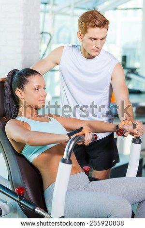 Helping her with exercising. Beautiful young woman working out in gym while confident instructor helping her - stock photo