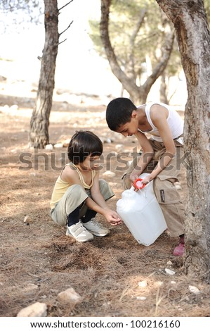 Helping in washing hands with water in nature, children summer camp - stock photo