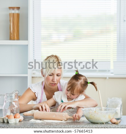 Helping mother and child baking cookies in kitchen - stock photo