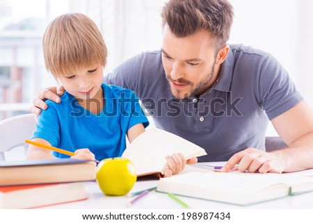 Helping son with homework. Confident young father helping his son with homework while sitting at the table together  - stock photo
