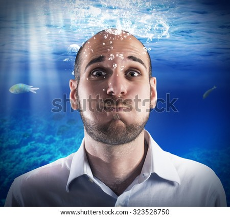 Helpless man holds his breath under water
