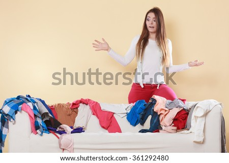 Helpless woman standing behind on sofa couch in messy living room shrugging. Young girl surrounded by many stack of clothes. Disorder and mess at home. - stock photo