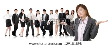 Helpless young business woman shrugs her shoulders in front of her team on white background. - stock photo