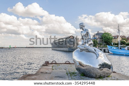 "HELSINGOR (Elsinore), DENMARK - 2014 JUN 10: Sculpture ""Han"" (art. Michael Elmgrin and Ingar Dragset). The sculpture mirror repeats the pose of the Mermaid, but on the stone sits a naked young man."