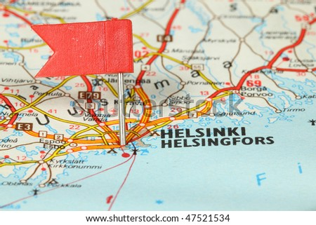 Helsinki - famous city in Finland. Red flag pin on an old map showing travel destination. - stock photo