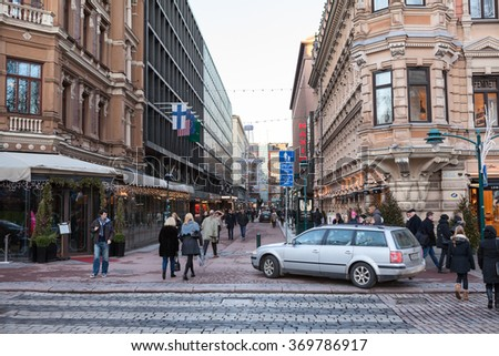 HELSINKI, FINLAND - CIRCA, DEC, 2015: The Pohjoiesplanadi street with walking people at Christmas holidays. December weather without snow is at Christmas eve. Cityscape of Helsinki city