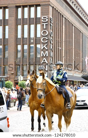 HELSINKI, FINLAND - JUNE 30: Mounted police protect people taking part in the annual Helsinki Pride gay parade in Helsinki, Finland on June 30, 2012. - stock photo