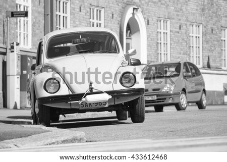 Helsinki, Finland - May 7, 2016: Old yellow Volkswagen beetle is parked on a roadside, front view, black and white photo - stock photo