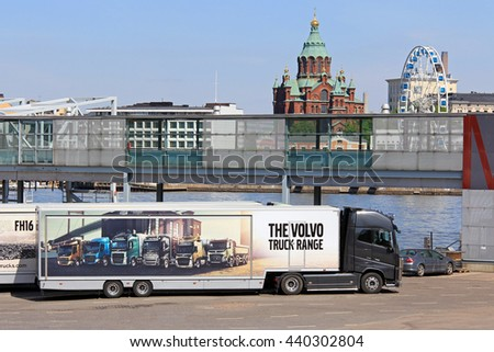 HELSINKI, FINLAND - MAY 24, 2016: Volvo FH16 750 semi parked at Olympic terminal with Uspenski Cathedral and Sky Wheel Helsinki on the background. The trailer shows the Volvo truck range.  - stock photo