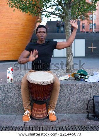Helsinki, Finland - Sept. 27, 2014: African Street Artist playing traditional West African drum Djembe, at the streets of Helsinki.