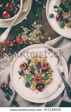 Helthy breakfast of homemade granola with yogurt and berries on rustic background - retro style toned