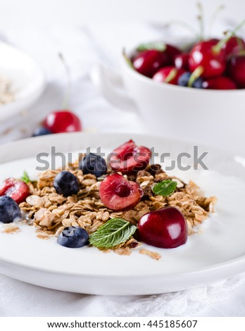 Helthy breakfast of homemade granola with yogurt and berries on white background