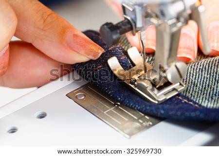 Hemming denim fabric on a sewing machine.
