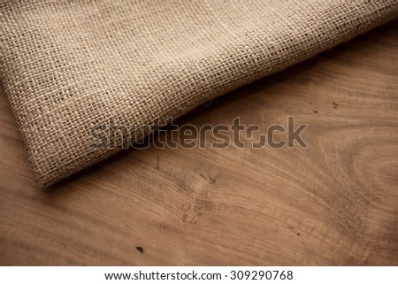 Hemp cloth on rustic wooden table. Shallow depth of field. - stock photo