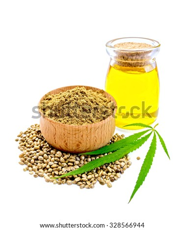 Hemp flour in a bowl, beans and green leaf of hemp, hemp seed oil in a glass jar isolated on white background - stock photo