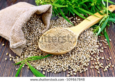 Hemp flour in a spoon, the grain in the bag and on the table,  leaves and stalks of cannabis on the background of dark wood planks