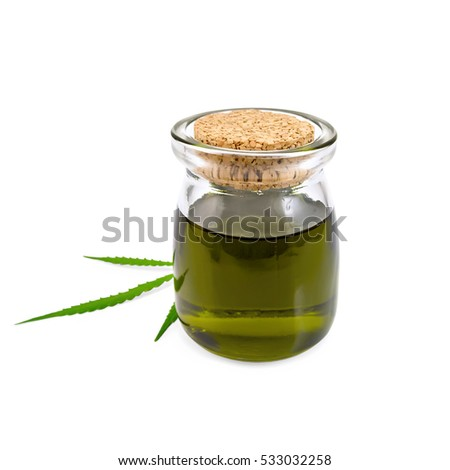 Hemp oil in a glass jar with a leaf isolated on white background