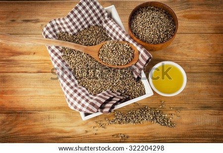 Hemp seeds and hemp oil on a wooden background. Top view - stock photo