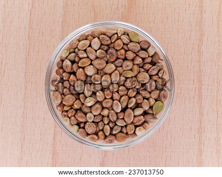 hemp seeds in a bowl on a wooden plate - stock photo