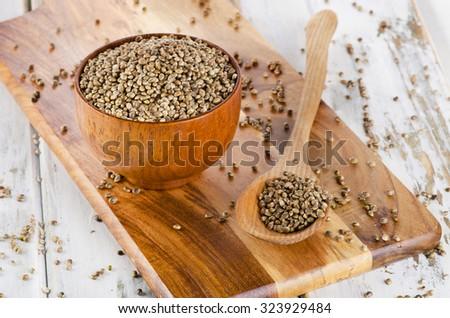 Hemp seeds on wooden board. Selective focus - stock photo