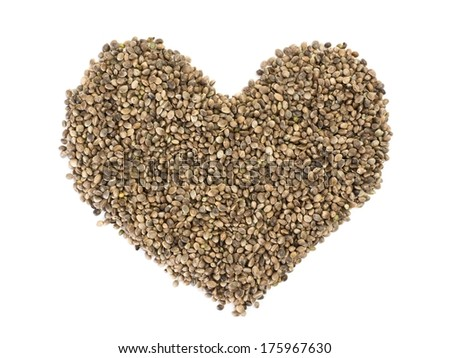 Hemp seeds shaped as a heart on white background - stock photo