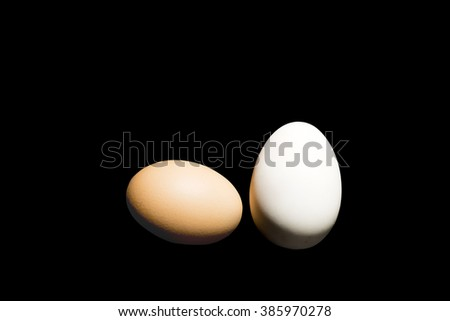 Hen and duck eggs on isolated black background and spacing for text