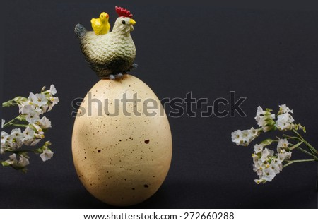 Hen with chick on her back sitting on huge egg framed with flowers - stock photo