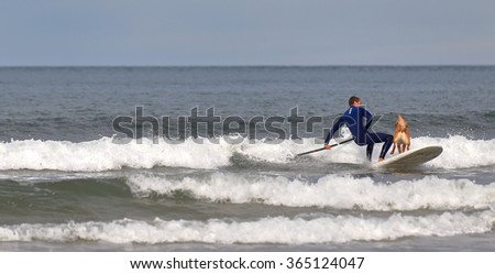 HENDAIA,FRANCE-JANUARY 17, 2016: Young surfer practice paddle surf with his dog on a wintry Sunday on January 17, Hendaia,France.