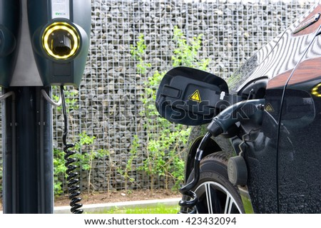 HENGELO, THE NETHERLANDS - MAY 17, 2016: An electric car is parked at a parking spot and is being recharged at a power station.