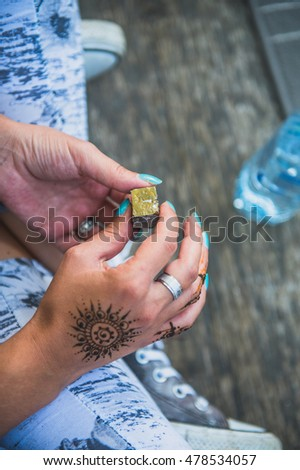Henna mandala tattoo on women hands. Traditional Indian decorative art. Holding crystal stone for relaxation.