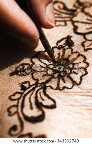 Henna tattoo drawing with herbal dye on foot floral design macro closeup