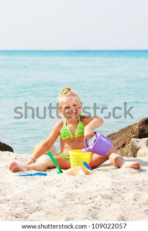 Heppy Little girl playing on the beach with bucket and spade